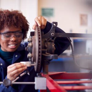 Female Student Working On Car Brakes On Auto Mechanic Apprenticeship Course At College