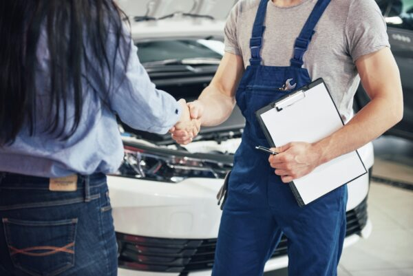 husband car mechanic and woman customer make an agreement on the repair of the car